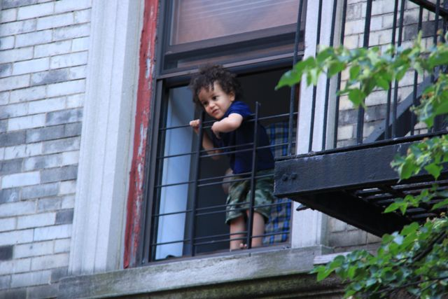 Open window with little boy standing