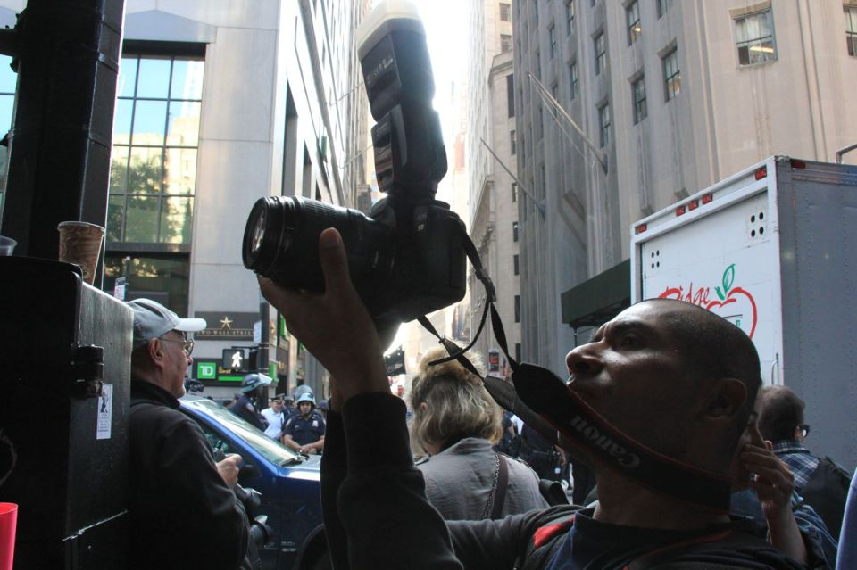 Man taking photo in crowded NYC street