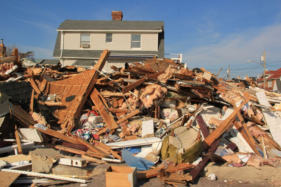 Damaged household goods and furniture piled up on Rockaway Beach
