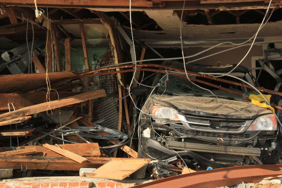 Crushed car amidst housing damage Rockaway Beach