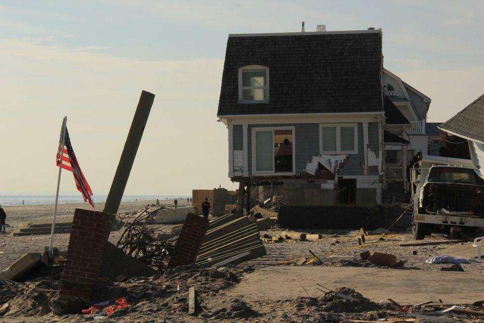 Rockaway beach and house damage with US flag