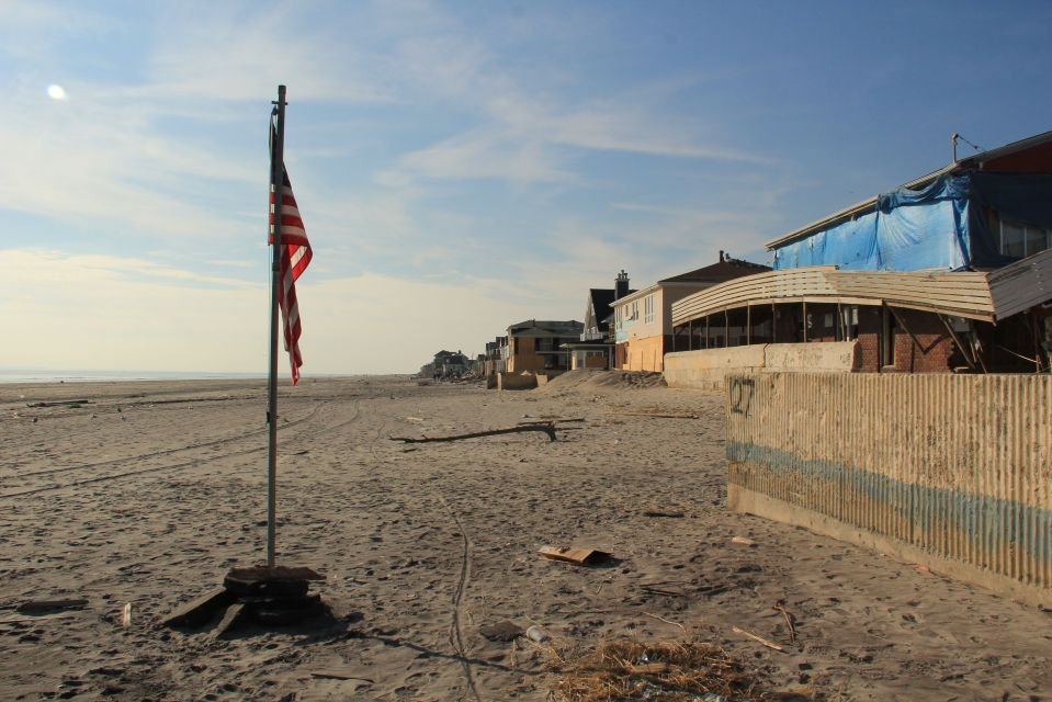 US flag on Rockaway Beach near damaged houses