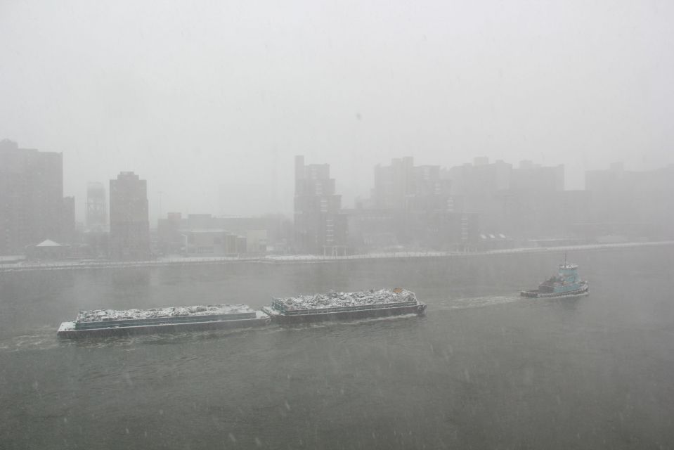 Tug hauling load on East River New York in snow