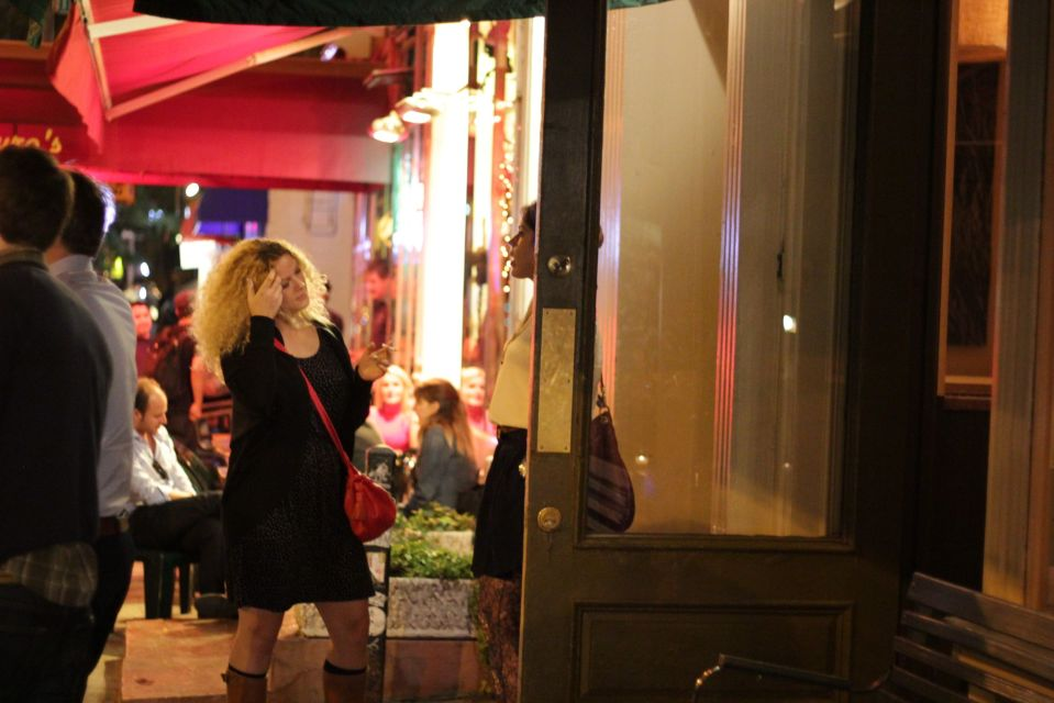 Girl smoking cigarette outside NY restaurant at night