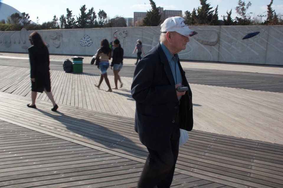 Older man in suit, baseball cap, transistor radio walking on Coney Island promenade