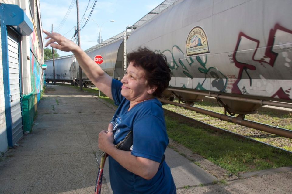 Martha ppointing something out with train going by, Hunts Point, the bronx