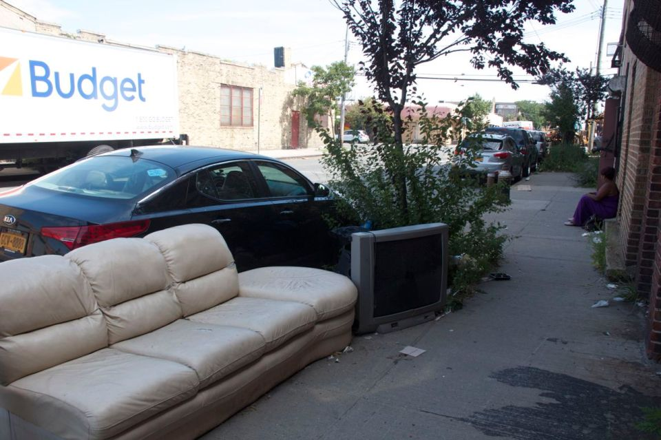 Hunts Point, woman on step near sofa and tv on street