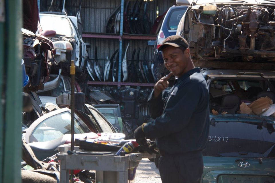 Man working in spare parts yard, hunt's point, the bronx, smiling