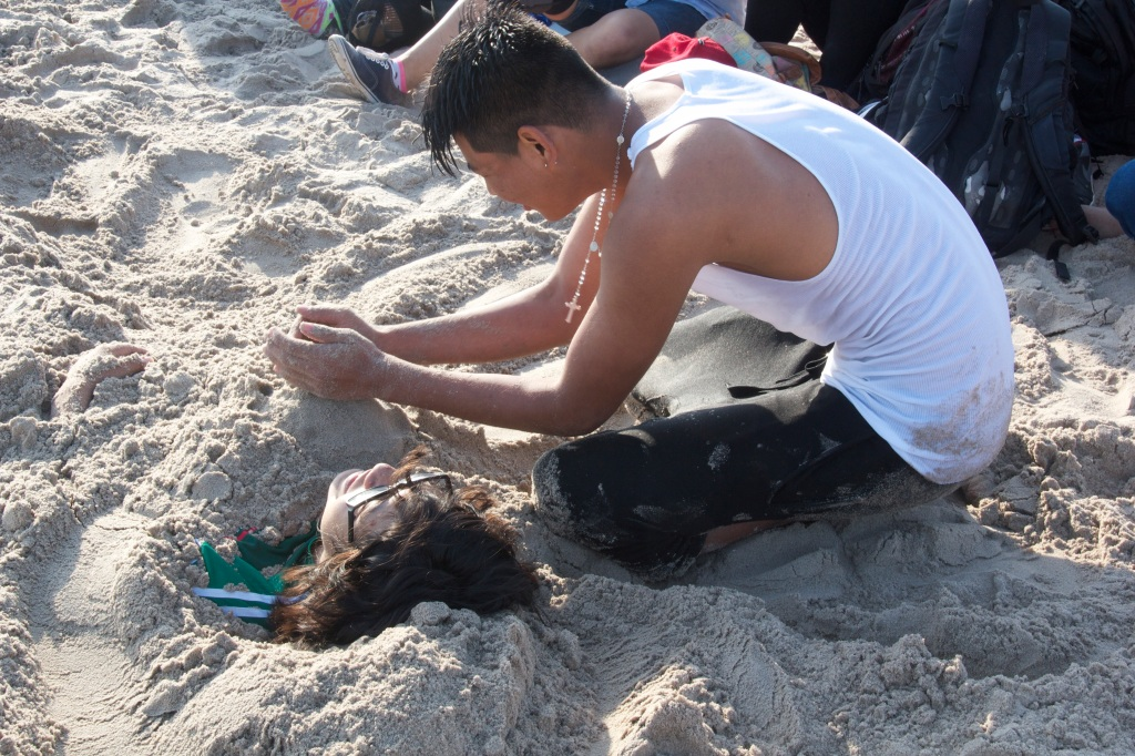 Young man building sand castle on girl in the sand, Coney Island.