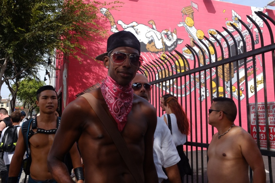 Bare chested men, pink wall, graffiti, Folsom St Fair