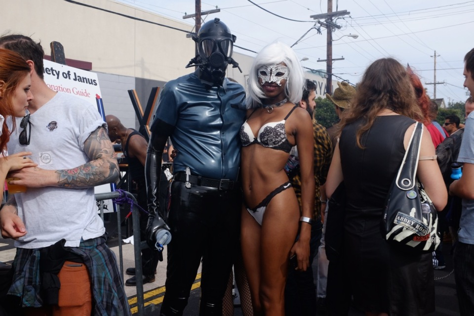 Couple dressed up at Folsom Street Fair. Him - leather, her - bikini.