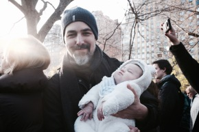 Father and baby in crowd at Strawberry Fields Central Park