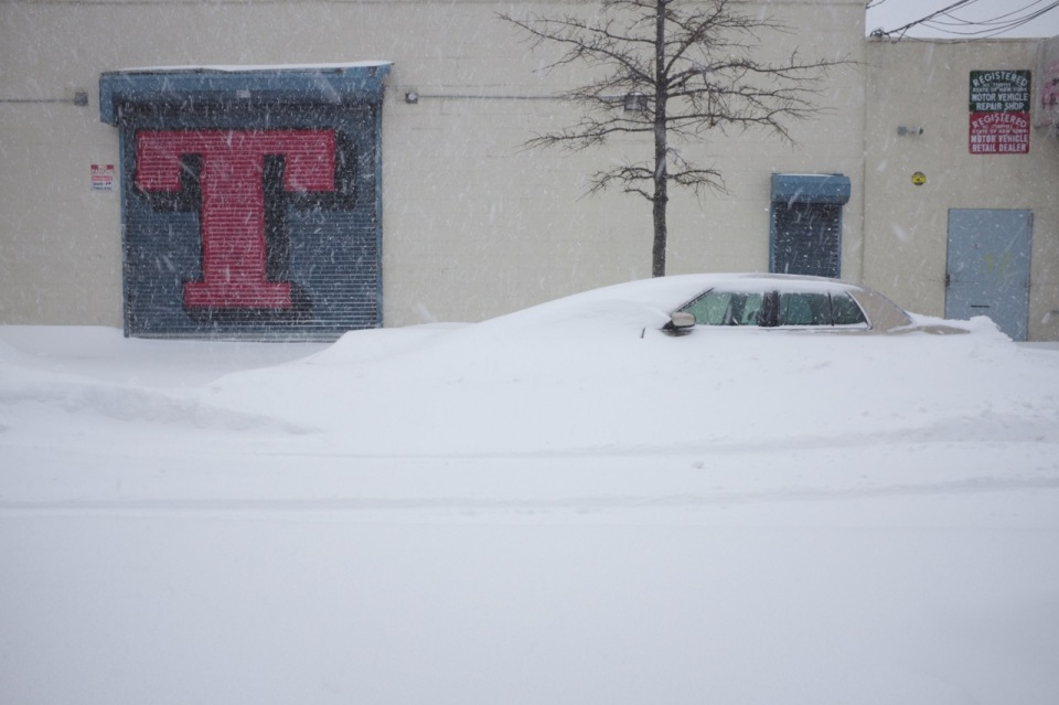 Vintage car buried in snow with nearby graffiti south bronx
