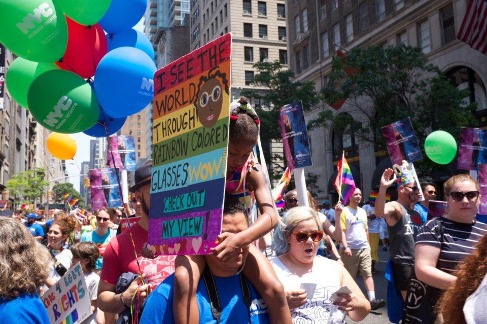 Balloons and rainbow sign in NYC Pride 2016 crowd