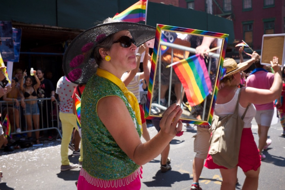 Woman with mirror marching in NYC pride 2016