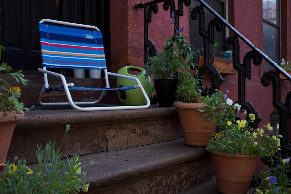 Chair on stoop with potted plants