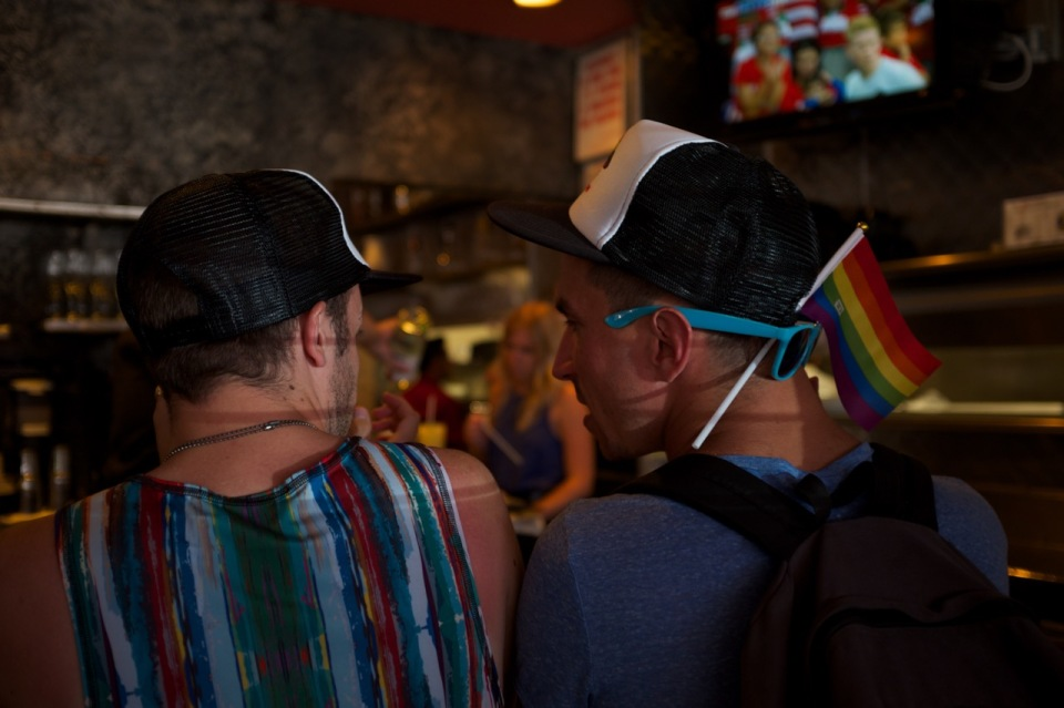 men in bar with rainbow flags NYC pride 2016